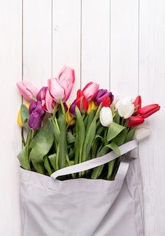Borsa in tessuto grigio piena di tulipani colorati