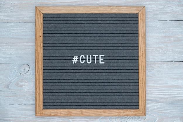Lettere in feltro grigio con la parola inglese cute e il segno dell'hashtag