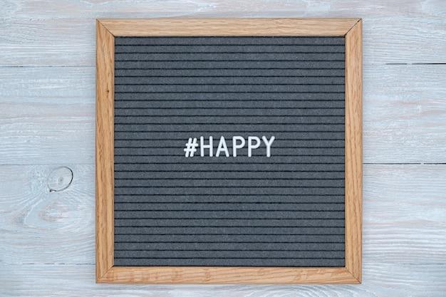 Lettere di lavagna in feltro grigio con la parola inglese happy e il segno dell'hashtag