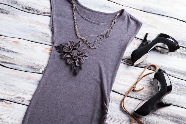 Top applique fiore grigio. scarpe e collana nere del tallone. capo da donna con scollo rotondo. top senza maniche su mensola in legno.