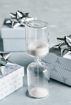 Scatole regalo grigie con fiocchi argentati e clessidra