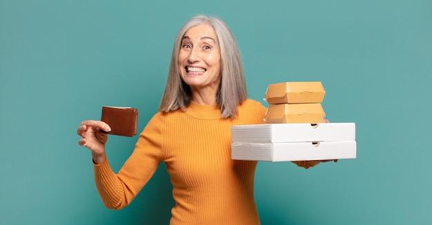 Donna graziosa dei capelli grigi che tiene cibo da asporto e portafoglio