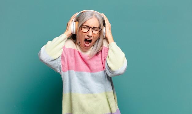 Donna graziosa dei capelli grigi che ascolta musica con le sue cuffie