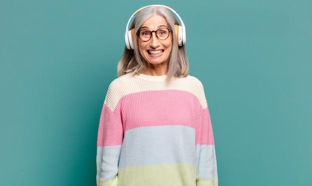 Bella donna dai capelli grigi che ascolta musica con le sue cuffie