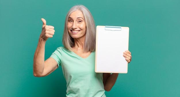 Donna graziosa dei capelli grigi che mostra un pezzo di carta vuoto
