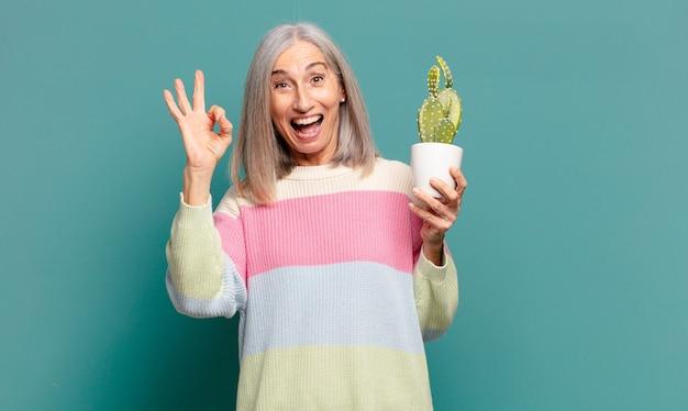 Bella donna con i capelli grigi con un cactus