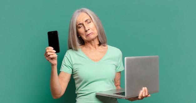 Donna graziosa dei capelli grigi con una cella e un computer portatile