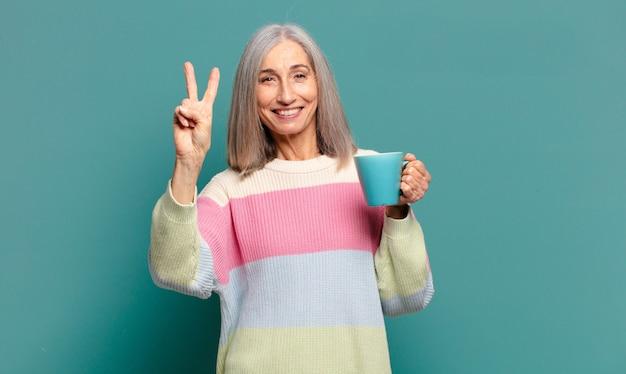 Bella donna dai capelli grigi con una tazza di caffè