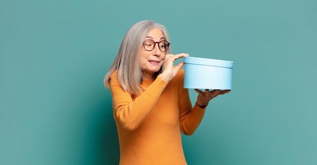 Bella donna capelli grigi con una confezione regalo