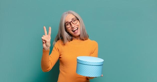 Bella donna con i capelli grigi con una confezione regalo