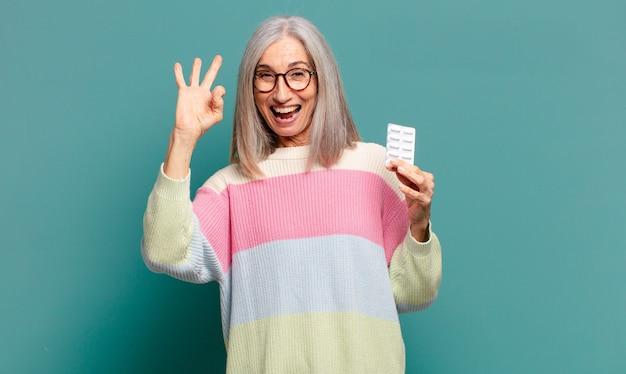 Bella donna dai capelli grigi con pillole per la malattia