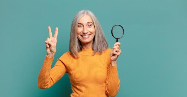 Bella donna dai capelli grigi con una lente d'ingrandimento