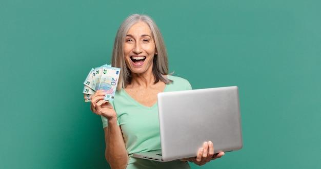 Donna graziosa dei capelli grigi con soldi e un computer portatile