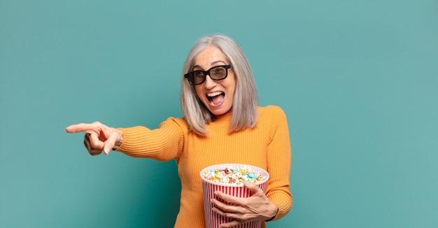 Bella donna con i capelli grigi con un secchio di pop corn
