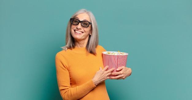 Bella donna dai capelli grigi con un secchio di pop corn