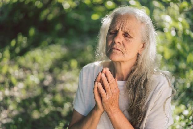 La nonna dai capelli grigi sta pregando all'aperto.