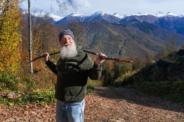 Un uomo dai capelli grigi con la barba conquista la vetta, il concetto di turismo e svago nella vecchiaia