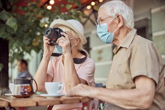 Uomo dai capelli grigi con una maschera facciale seduto accanto a una fotografa in un caffè di strada