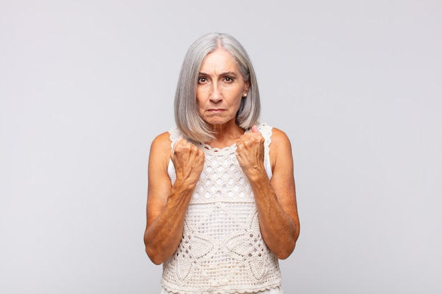 Donna dai capelli grigi che sembra sicura, arrabbiata, forte e aggressiva, con i pugni pronti a combattere in posizione di boxe