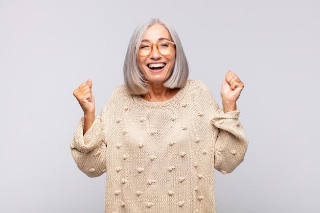 Donna dai capelli grigi che sembra estremamente felice e sorpresa, celebrando il successo, gridando e saltando
