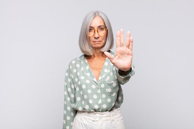 Donna dai capelli grigi che sembra seria, severa, dispiaciuta e arrabbiata che mostra il palmo aperto che fa il gesto di arresto