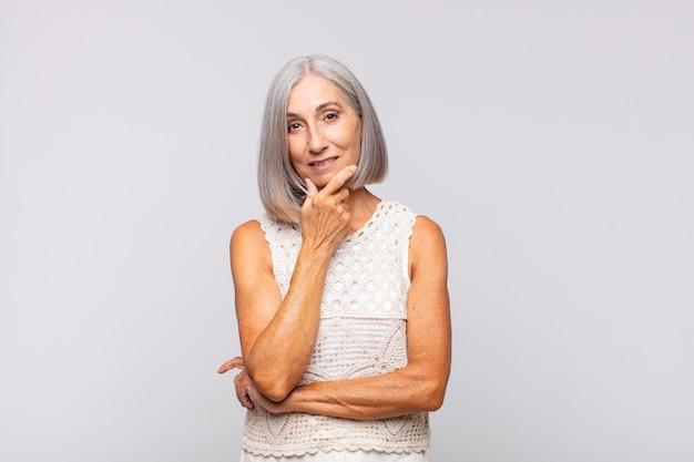 Donna dai capelli grigi che sembra seria, premurosa e diffidente, con un braccio incrociato e una mano sul mento, opzioni di ponderazione