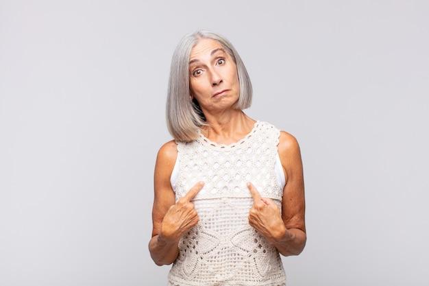 Donna dai capelli grigi che indica se stessa con uno sguardo confuso e interrogativo, scioccata e sorpresa di essere stata scelta