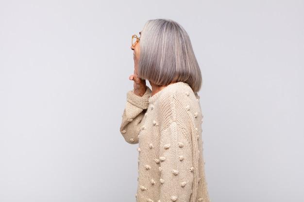 Vista di profilo della donna dai capelli grigi, che sembra felice ed eccitata, gridando isolata