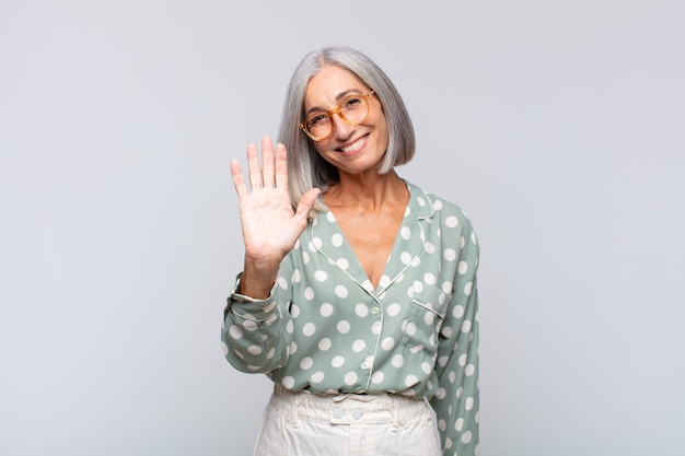 Donna dai capelli grigi che sorride allegramente e allegramente, agitando la mano, dandoti il benvenuto e salutandoti o salutandoti