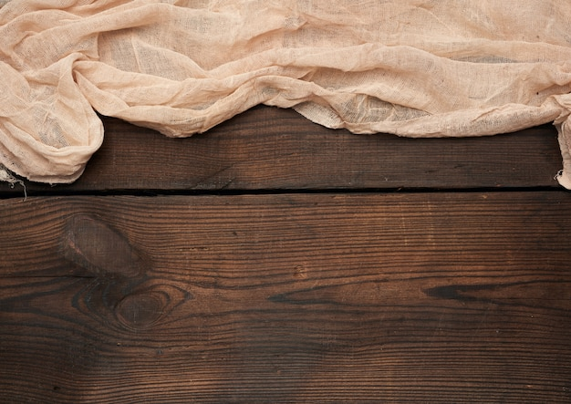 L'asciugamano grigio del tessuto della cucina ha piegato su una tavola di legno marrone dai bordi anziani, vista superiore, spazio vuoto