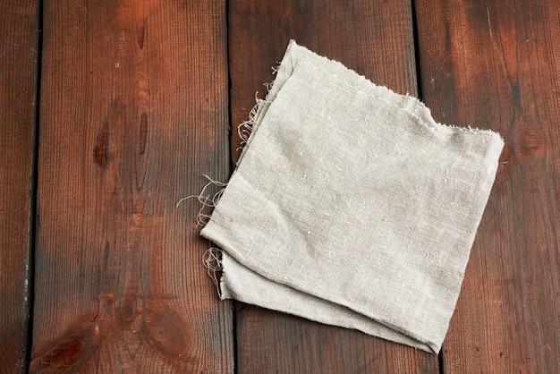 Asciugamano tessile da cucina grigio piegato su un tavolo di legno marrone