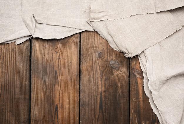 Asciugamano da cucina grigio su fondo di legno marrone, vista dall'alto, copia dello spazio