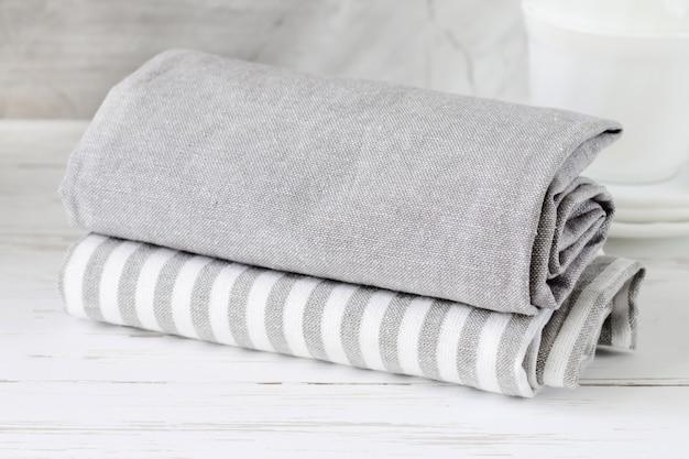 Asciugamani di cucina grigi su una tavola di legno bianca