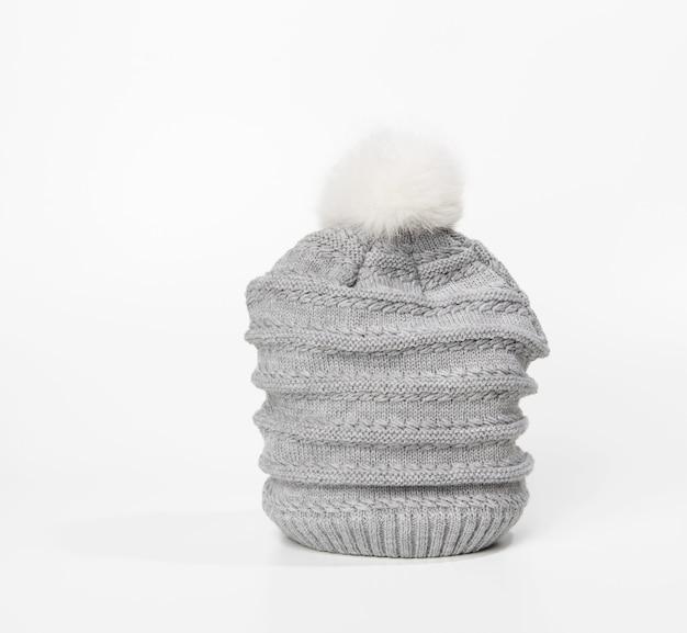 Cappello lavorato a maglia grigio con pompon su superficie bianca, abbigliamento caldo e comodo