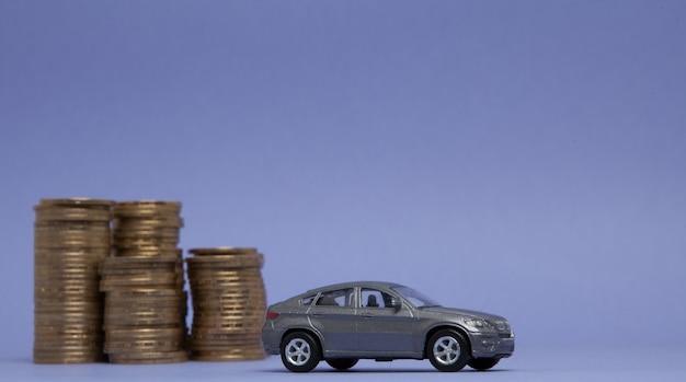 Un modello grigio di una macchina con monete sotto forma di un istogramma su uno sfondo viola. concetto di prestito, risparmio, assicurazione.