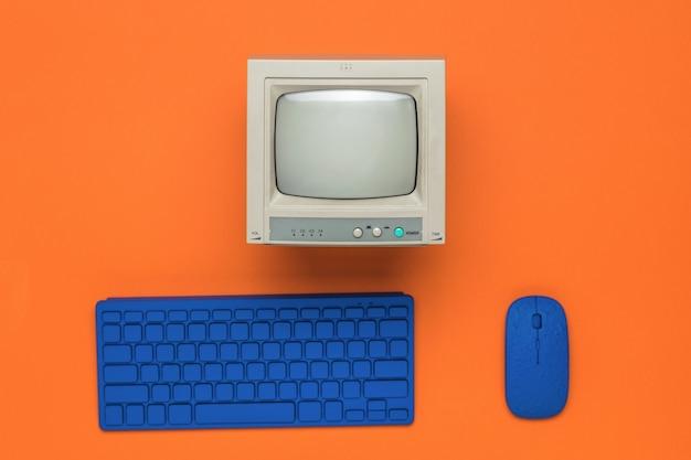 Un monitor grigio e una tastiera e un mouse blu su uno sfondo arancione.
