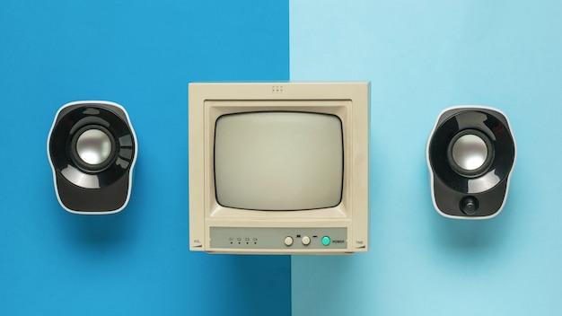 Un monitor grigio e due altoparlanti su uno sfondo a due colori. disposizione piatta.