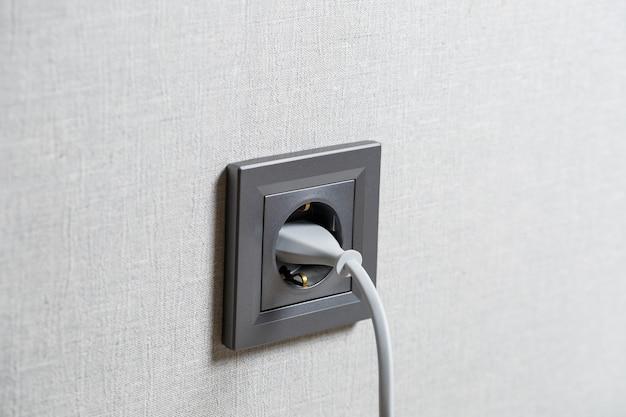 Una presa grigia sul muro che include un dispositivo con un cavo bianco. ricarica da una presa di corrente