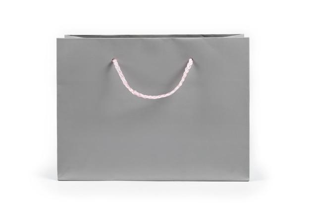 Shopping bag di carta grigia su sfondo chiaro. spazio libero per il testo. shopping, vendita, sorpresa o concetto di regalo.