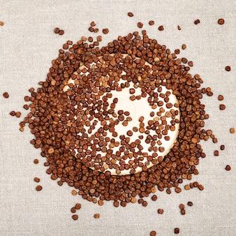 Sfondo di cibo naturale di piselli grigi. piccoli chicchi di semi di fagioli di legumi sparsi su tela di sacco.