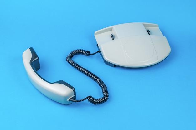 Un telefono grigio con il ricevitore spento su sfondo blu. mezzi di comunicazione retrò.
