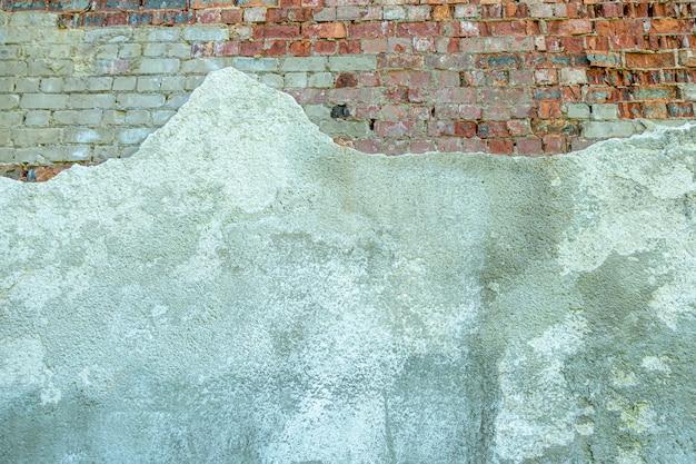 Vecchio muro di mattoni intonacato grigio con pezzi di stucco scheggiato muro di mattoni rossi e bianchi del grunge con...