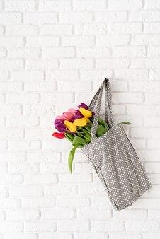 Borsa in tessuto grigio a pois piena di tulipani colorati