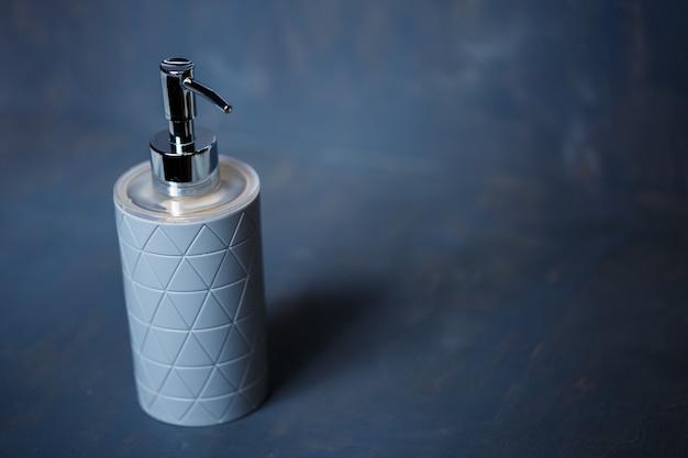 Dispenser di sapone grigio con tappo in metallo su tavolo grigio