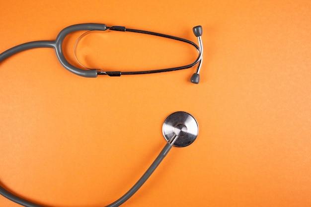 Stetoscopio grigio su superficie arancione