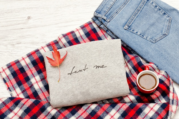 Maglione grigio con scritta, plaid, jeans, tazza da caffè e foglie autunnali. concetto alla moda