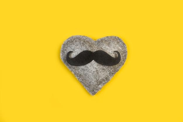 Un cuore di tessuto grigio con baffi neri su sfondo giallo