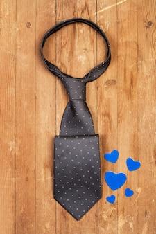 Una cravatta grigia e cuori blu su un tavolo di legno
