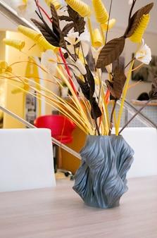 Un vaso grigio stampato su una stampante pubblicitaria si trova su un tavolo all'interno