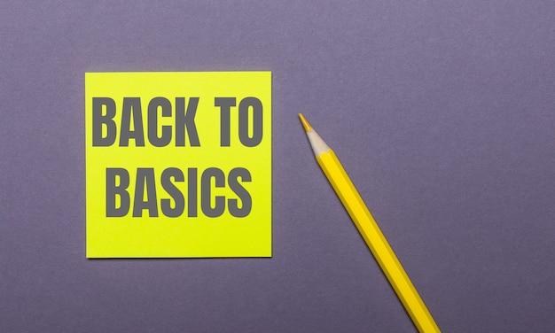 Su una parete grigia, una matita gialla brillante e un adesivo giallo con la scritta back to basics